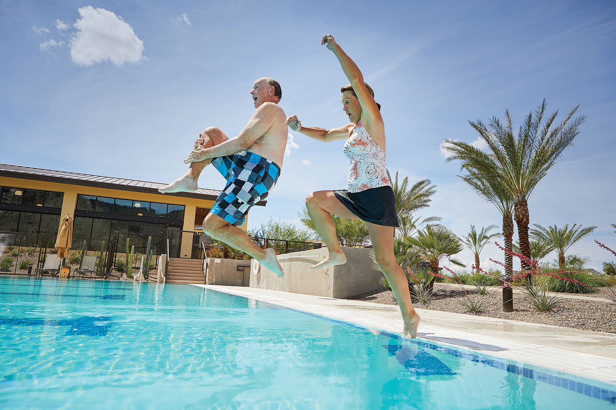 active adults jumping in a pool